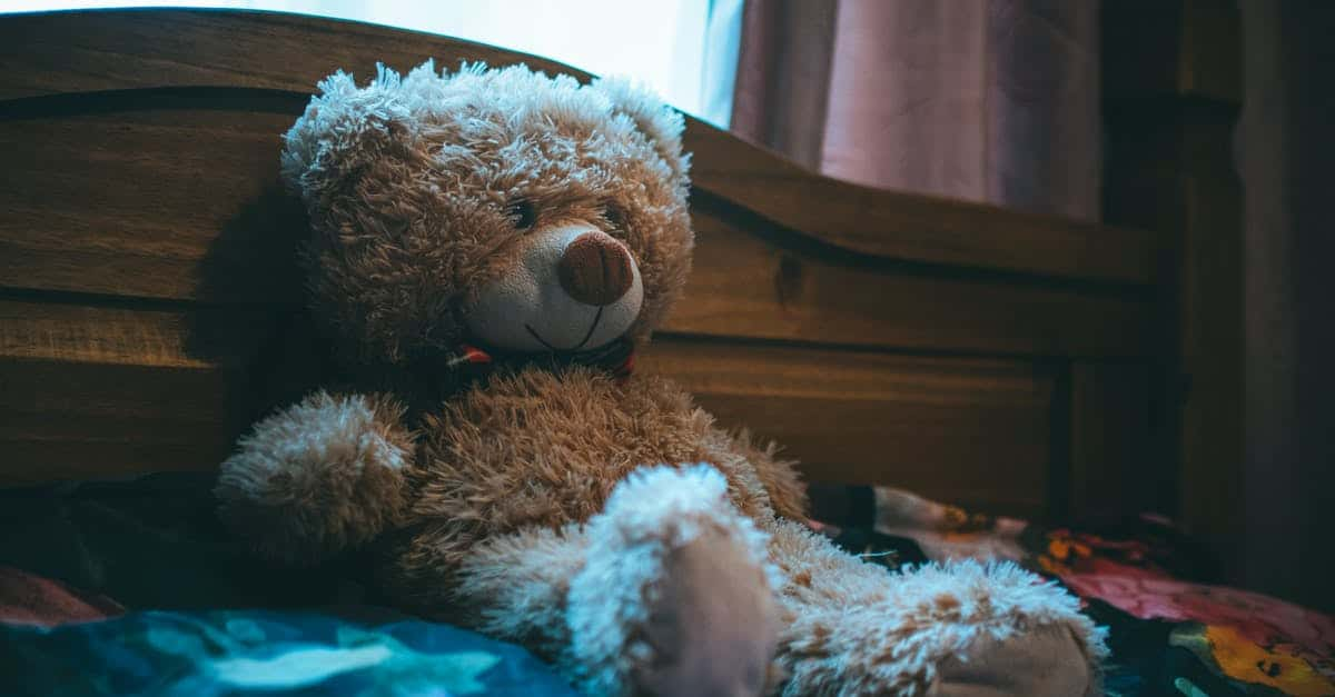 A large brown teddy bear sitting on top of a bed